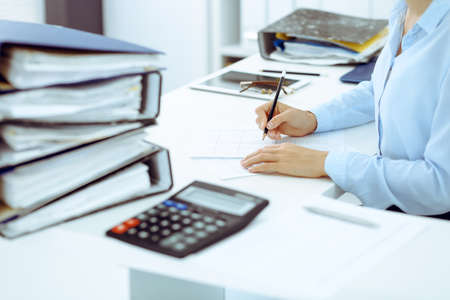 Unknown female bookkeeper or financial inspector calculating or checking balance, making report, close-up. Internal Revenue Service at work with financial document. Tax and audit concept. Banco de Imagens