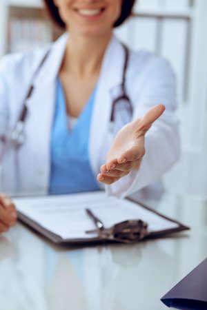 Closeup of medicine doctor offering helping hand or handshake. Partnership and trust concept Foto de archivo - 129482949