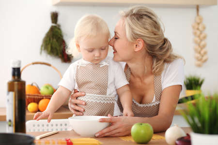 Happy mother and little daughter cooking in kitchen. Spending time all together, family fun concept Foto de archivo - 129482950