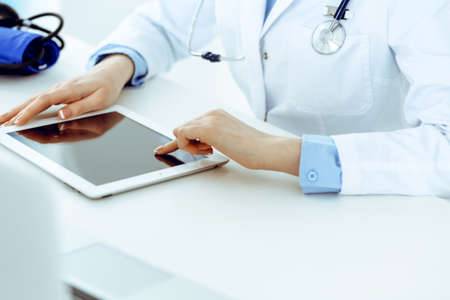 Doctor working table. Woman physician using tablet computer while sitting in hospital office close-up. Healthcare, insurance and medicine concept
