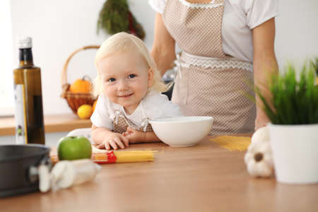 Happy mother and little daughter cooking in kitchen. Spending time all together, family fun concept Foto de archivo - 129483733