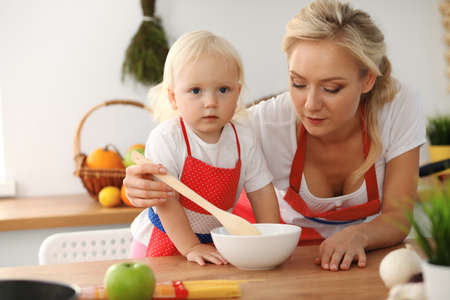 Happy mother and little daughter cooking in kitchen. Spending time all together, family fun concept Foto de archivo - 129483723