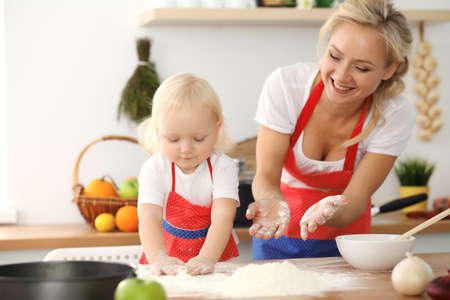 Little girl and her blonde mom in red aprons playing and laughing while kneading the dough in kitchen. Homemade pastry for bread, pizza or bake cookies. Family fun and cooking concept Foto de archivo - 129483732
