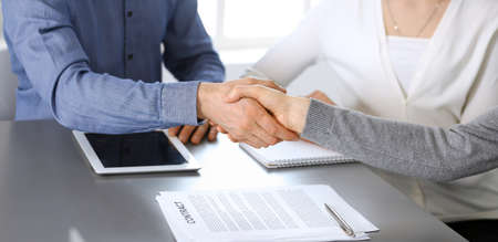 Group of business people shaking hands after discussing questions at meeting in modern office. Handshake close-up. Teamwork, partnership and agreement in business concept