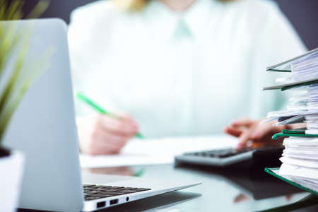 Contador o inspector financiero haciendo informe, calculando o comprobando el saldo. Concepto de servicio de auditoría e impuestos. Fondo de imagen de color verde.