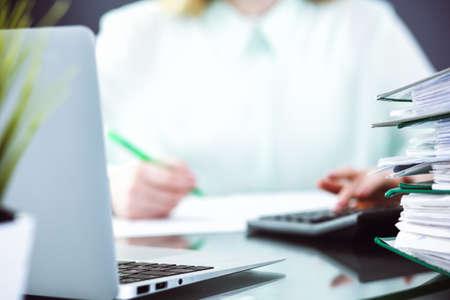 Księgowy lub inspektor finansowy sporządzający raport, obliczający lub sprawdzający saldo. Koncepcja usługi audytu i podatków. Zielone kolorowe tło obrazu.