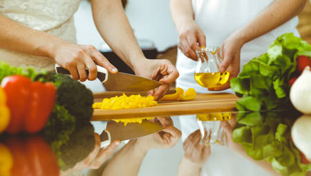 Closeup of human hands cooking in kitchen. Mother and daughter or two female friends cutting vegetables for fresh salad. Friendship, family dinner and lifestyle concepts.