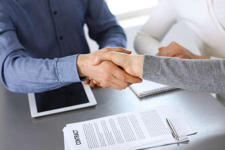 Group of business people shaking hands after discussing questions and achieving agreement at meeting in modern office. Handshake close-up. Teamwork, partnership and business concept. Foto de archivo - 129470281