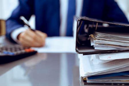 Reliures avec des papiers en attente de traitement avec un homme d'affaires ou un comptable de retour dans le flou. Budget de planification comptable. Audit, assurance et concept d'entreprise