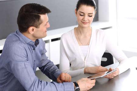 Fröhlicher lächelnder Geschäftsmann und Frau, die mit Computer im modernen Büro arbeiten. Kopfschuss bei Besprechung oder Arbeitsplatz. Teamwork, Partnerschaft und Geschäftskonzept