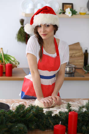 Young brunette woman cooking pizza or handmade pasta while wearing Santa Claus cap in the kitchen. Housewife preparing dough on wooden table