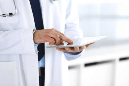 Dokter man die tabletcomputer gebruikt voor netwerkonderzoek of virtuele ziektebehandeling, handen close-up. Perfecte medische service in de kliniek. Moderne geneeskunde, medische gegevens en gezondheidszorgconcepten. Getinte foto