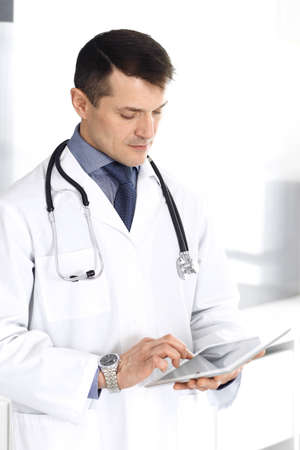 Doctor man using tablet computer for network research or virtual disease treatment. Perfect medical service in clinic. Happy future for modern medicine, medic data and healthcare concepts 写真素材