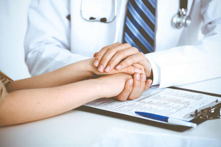 Hand of doctor reassuring her female patient. Concepts of medical ethics and trust in medicine