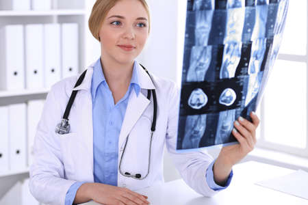 Doctor woman examining x-ray picture near window in hospital. Surgeon or orthopedist at work. Medicine and healthcare concept. Blue colored blouse of a therapist looks good 写真素材