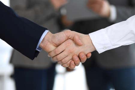 Geschäftsleute, die sich nach einem Treffen oder einer Verhandlung die Hände schütteln, während sie mit Kollegen stehen, Nahaufnahme. Gruppe unbekannter Geschäftsleute und Frauen im modernen Büro. Teamwork, Partnerschaft und Handschlagkonzept, getöntes Bild