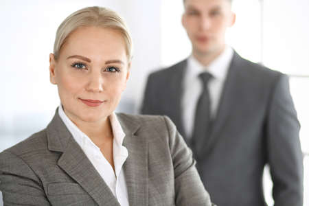 Business woman standing straight with colleague businessman in office, headshot. Success and corporate partnership concept Stock Photo