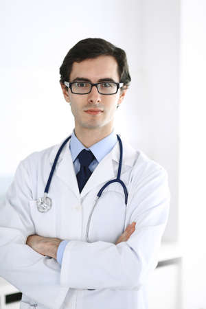 Doctor man standing straight with arms crossed. Perfect medical service in clinic. Happy future in medicine and healthcare Stock Photo