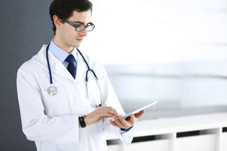Doctor man using tablet computer for network research or virtual disease treatment. Perfect medical service in clinic. Modern medicine, medic data and healthcare concepts