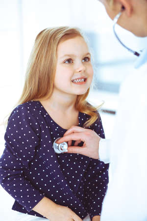Doctor examining a child patient by stethoscope. Cute baby girl at physician appointment. Medicine concept. Toned photo
