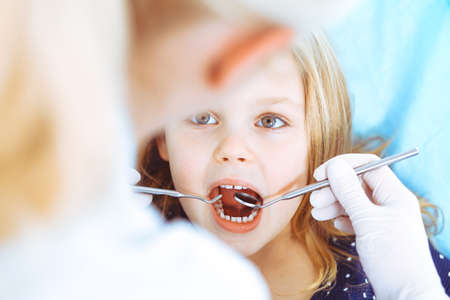 Little baby girl sitting at dental chair with open mouth during oral check up while doctor. Visiting dentist office. Medicine concept. Toned photo