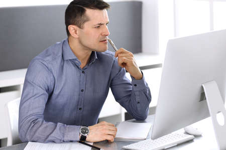 Businessman working with computer in modern office. Headshot of male entrepreneur or company director at workplace. Business concept Stock Photo