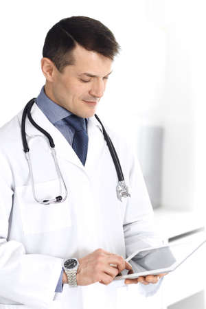 Doctor man using tablet computer for network research or virtual disease treatment. Perfect medical service in clinic. Happy future for modern medicine, medic data and healthcare concepts Stock Photo