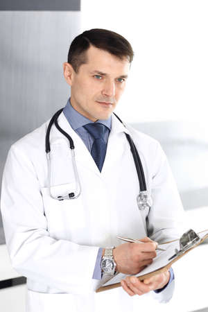 Doctor man using clipboard for filling up medication history records. Perfect medical service in clinic. Physician at work in hospital. Medicine and healthcare concepts
