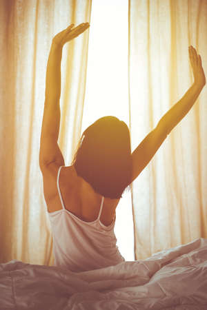 Woman stretching hands in bed after wake up, sun flare . Brunette entering a day happy and relaxed after good night sleep and back view. Concept of a new day and joyful weekend Stock Photo