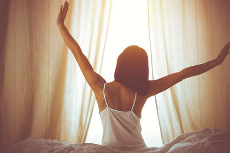 Woman stretching hands in bed after wake up, sun flare . Brunette entering a day happy and relaxed after good night sleep and back view. Concept of a new day and joyful weekend Archivio Fotografico - 133532029