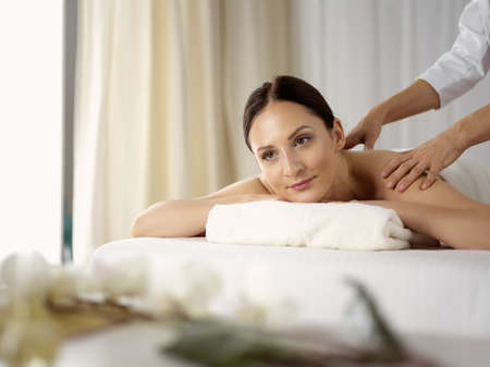 Pretty brunette woman enjoying procedure of back massage in spa salon. Beauty concept