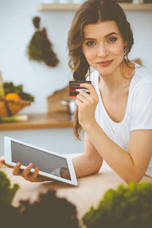 Young woman looking for a new recipe for cooking in a kitchen. Housewife is making online shopping by tablet computer and credit card Stock fotó