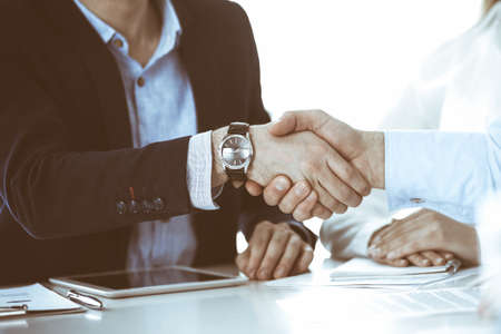Business people shaking hands at meeting or negotiation, close-up. Group of unknown businessmen and women in modern office. Teamwork, partnership and handshake concept, toned picture