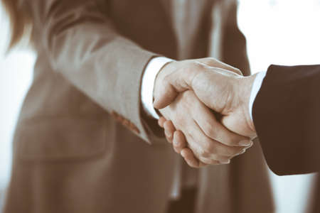 Business people shaking hands while standing with colleagues after meeting or negotiation, close-up. Group of unknown businessmen and women in modern office. Teamwork, partnership and handshake concept, toned picture