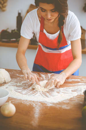 Young brunette woman cooking pizza or handmade pasta in the kitchen. Housewife preparing dough on wooden table. Dieting, food and health concept