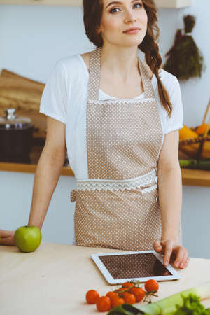 Young woman looking for a new recipe for cooking in a kitchen. Housewife is making online shopping by tablet computer and credit card Stok Fotoğraf