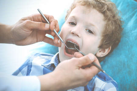 Doctor and patient child. Boy having his teeth examined with dentist. Medicine, health care and stomatology concept