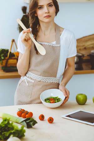 Young brunette woman cooking in kitchen. Housewife holding wooden spoon in her hand. Food and health concept