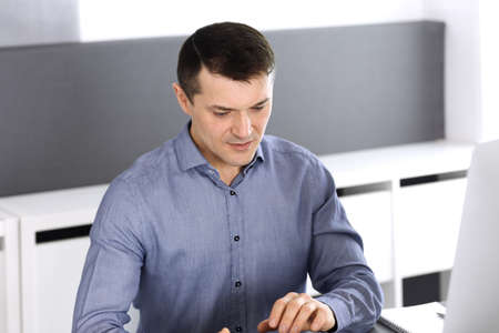 Businessman working with tablet computer in modern office. Headshot of male entrepreneur or company director at workplace. Business concept
