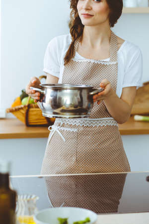 Young brunette woman cooking soup in kitchen. Food and health concept Stok Fotoğraf