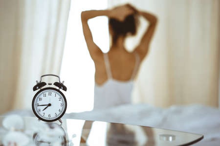 Woman stretching hands in bed after wake up, sun flare . Brunette entering a day happy and relaxed after good night sleep and back view. Concept of a new day and joyful weekend Banco de Imagens