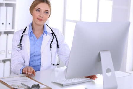 Young woman doctor at work in hospital looking at desktop pc monitor. Physician controls medication history records and exam results. Medicine and healthcare concept