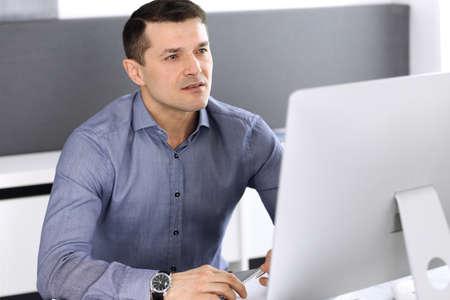Geschäftsmann, der mit Computer im modernen Büro arbeitet. Kopfschuss eines männlichen Unternehmers oder Firmendirektors am Arbeitsplatz. Unternehmenskonzept
