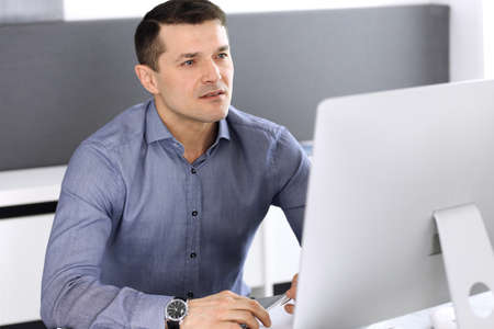 Hombre de negocios que trabaja con la computadora en la oficina moderna. Foto de cabeza del empresario masculino o director de la empresa en el lugar de trabajo. Concepto de negocio