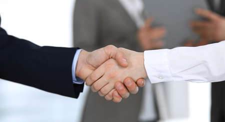 Business people shaking hands while standing with colleagues after meeting or negotiation, close-up. Group of unknown businessmen and women in modern office. Teamwork, partnership and handshake concept, toned picture.