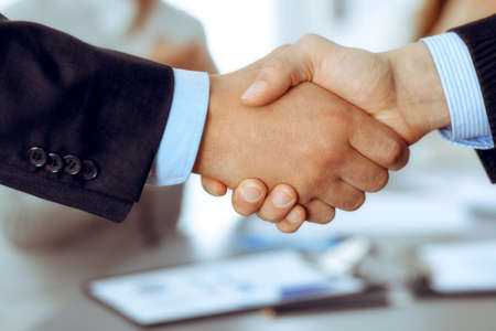 Business people shaking hands at meeting while theirs colleagues clapping and applauding. Group of unknown businessmen and women in modern white office. Success teamwork, partnership and handshake concept Archivio Fotografico