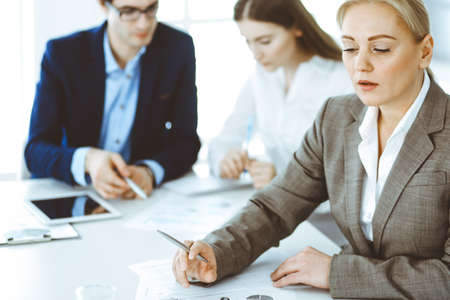 Headshot of business woman at negotiation. Group of business people discussing questions at meeting in modern office. Teamwork, partnership and business concept