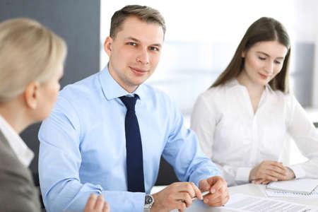 Groep zakenmensen die vragen bespreken tijdens een bijeenkomst in een modern kantoor. Headshot van zakenman bij onderhandeling. Teamwerk, partnerschap en bedrijfsconcept Stockfoto