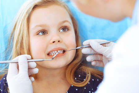 Little baby girl sitting at dental chair with open mouth during oral check up while doctor. Visiting dentist office. Medicine concept. Toned photo Archivio Fotografico - 137434115
