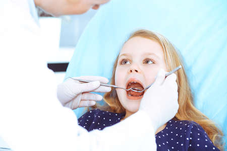 Little baby girl sitting at dental chair with open mouth during oral check up while doctor. Visiting dentist office. Medicine concept. Toned photo Archivio Fotografico - 137434665